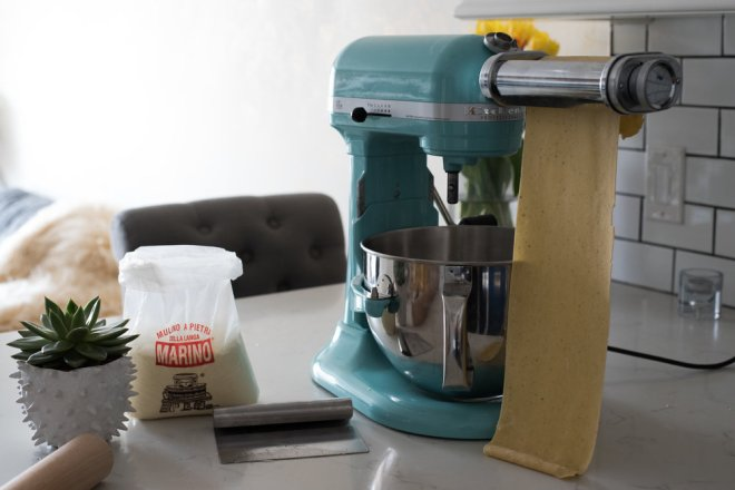 Here I am, rolling out dough using this awesome kitchen-aid pasta tool. It's an absolute must have for all your homemade pasta sheets, and it's 100x easier than using a traditional hand crank pasta machine.