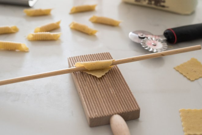 The gentle yet firm folding technique on the board that creates the grooves in the pasta and seals the edges.